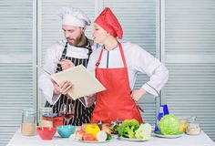 Culinary family concept. Couple in love cooking healthy recipe. Amateur cook read book recipes. Improve cooking skill stock photo