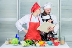 Culinary family concept. Couple in love cooking healthy recipe. Amateur cook read book recipes. Improve cooking skill. Book recipes. Helpful culinary book royalty free stock photo