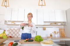 Culinary girl holds smartphone in hands and takes photo of veget. Charming woman using mobile gadget records video of cooking process and photographs composition Royalty Free Stock Photo
