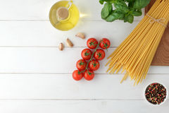 Culinary pasta background with dry bucatini, fresh basil and tomatoes on white wooden table. royalty free stock photography