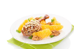 Culinary roast duck. Culinary roast duck with oranges and nuts on plate on white background. Delicious festive eating Stock Photo
