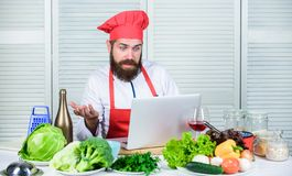 Culinary school. Hipster in hat and apron learning how to cook online. Culinary education online. Elearning concept. Man. Chef searching internet recipe cooking stock image
