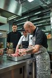 Culinary school. Professional chef with tattoos on his hands holding a red meat and teaching assistants how to choose. Right. Preparing food stock image