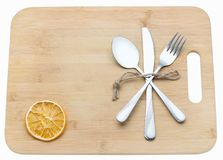 Cutlery crisscrossing on a wooden chopping board. Culinary background with cutting board. royalty free stock photo