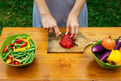 Culinary workshop. Vegetable salad. With own hands in the courtyard of a private house. Preparation of vegetable salad on the background of home garden and pool Stock Photography