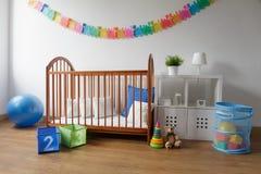 Culla di legno in camera da letto accogliente Immagine Stock
