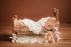 Culla per un neonato su un fondo marrone con i giocattoli e una coperta bianca, fondo Fotografia Stock