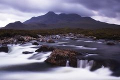 The Cullin hills and river. Evening light falls on the distant cullin hills. The photo is taken over a raging mountain stream with large rocks dominating the stock image