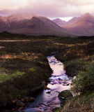 The Cullin hills and river. Morning sunlight lights the distant cullin hills in a warm glow. The photo is taken over a raging mountain stream with large rocks royalty free stock photo