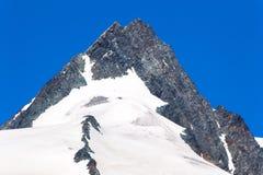 Culmine con neve sotto e un chiaro cielo blu qui sopra Fotografia Stock