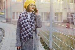 ?culos de sol vestindo de uma mo?a atrativa em um revestimento que anda abaixo da rua e que fala no telefone e nos sorrisos foto de stock
