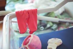 Culottes et petit chapeau de bébé dans le berceau d'hôpital pour des nouveaux-nés image stock