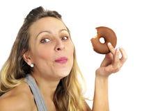 Culpable feliz de la mujer de la consumición del buñuelo travieso atractivo joven del chocolate para la nutrición malsana Fotos de archivo libres de regalías
