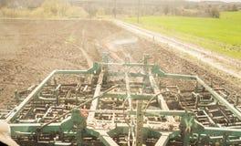 Cultivador detrás del tractor en suelo arado cerca del campo verde Imágenes de archivo libres de regalías