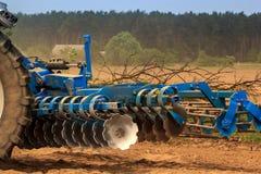 cultivador en el camino de tierra por el campo arado contra pueblo Fotografía de archivo libre de regalías