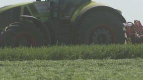 Cultivando la máquina segador del combaine que se mueve en el campo agrícola para cosechar la tierra Maquinaria agrícola en la almacen de metraje de vídeo
