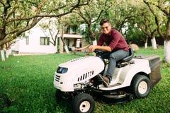 Cultivando un huerto, recorte de la hierba en curso Trabajador de sexo masculino que usa el cortacésped y la sonrisa imagenes de archivo