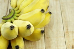 Cultivate Asian yellow banana on wood background. Royalty Free Stock Photos