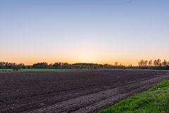 Cultivated fields in countryside with dark and wet soil for agriculture. Tractor made plotting furrows on the ground royalty free stock photo