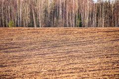 Cultivated fields in countryside with dark and wet soil for agriculture. Tractor made plotting furrows on the ground royalty free stock image