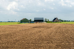 Cultivated soil in front of a modern Dutch farmhouse with barns. Overview of a modern Dutch farmhouse with barns and cultivated soil in front of it. It is a royalty free stock image