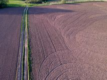 Cultivated spring agriculture field and farm road, aerial. Plowed cultivated spring time agriculture field and bad farm road, aerial view royalty free stock photography