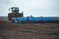 Cultivateur de semis et culture de terre avec le tracteur photographie stock libre de droits