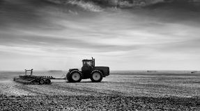 Cultivating a field in rural landscape Royalty Free Stock Image