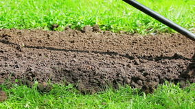 Cultivating flower bed with a rake stock footage