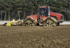 Cultivating land and drilling Maize Stock Photo