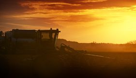 Cultivating in Sunset. Tractor Works on the Field. Agriculture Works Photography Collection Stock Image
