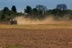 cultivator operates on ploughed field raises dust in spring Royalty Free Stock Photography