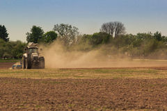 Cultivator operates on ploughed field raises dust in spring Royalty Free Stock Photos