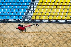 Cultivator stands on the sand in the middle of a sporty small stadium with blue and yellow seats of fans. Royalty Free Stock Photo