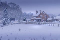 Cultive a casa de campo da casa durante a tempestade da neve do inverno do Natal fotos de stock royalty free