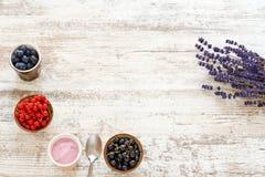 Cultive el yogur y las bayas frescas en una tabla de madera Espacio para el texto Imágenes de archivo libres de regalías