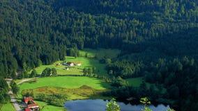 Cultive la casa en campo de hierba verde en montañas francesas metrajes