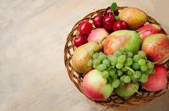 Cultive maçãs, peras, uvas e ameixas em uma placa de madeira de vime na tabela Colheita de frutos do outono Copie o espaço Imagem de Stock