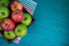 Cultive maçãs vermelhas e verdes orgânicas frescas na tabela de madeira na pasta Imagens de Stock