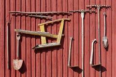 Cultive o equipamento velho que pendura em uma parede vermelha agricultura imagens de stock royalty free