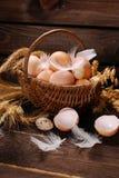 Cultive ovos na cesta de vime no fundo de madeira Imagens de Stock