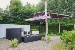 Cultive un huerto con muebles modernos del jardín, la charca de moda y el parasol Fotografía de archivo