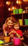 Cultiveer concept De moeder en de zoon cultiveren grond voor te kweken installatie De moeder en het kind cultiveren vuil voor ing stock fotografie