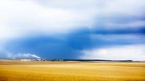 Cultivez avec de la fumée du pendant les nuages de tempête imminents Images libres de droits