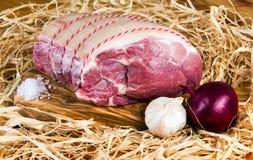 Cultivez l'épaule de porc sans os britannique sur la planche à découper et la paille, l'oignon, l'ail et le sel de mer Image stock
