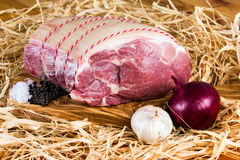 Cultivez l'épaule de porc sans os britannique sur la planche à découper et la paille, l'oignon, l'ail, le poivre noir et le sel d Images stock