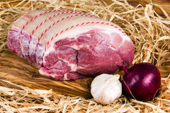 Cultivez l'épaule de porc sans os britannique sur la planche à découper et la paille, oignon, ail Images stock
