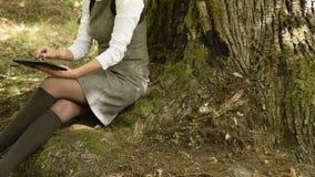 Cultivez la vue de la jeune femme universitarian atractive travaillant avec le comprimé en parc banque de vidéos