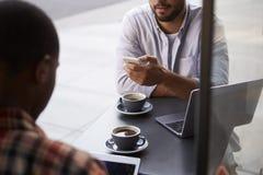 Cultivez le tir de deux amis masculins avec des cafés en dehors du café Photo stock