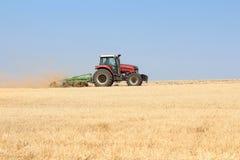 Cultivo de um campo de trigo em um trator em um dia ensolarado do verão Colheita na agricultura fotos de stock royalty free